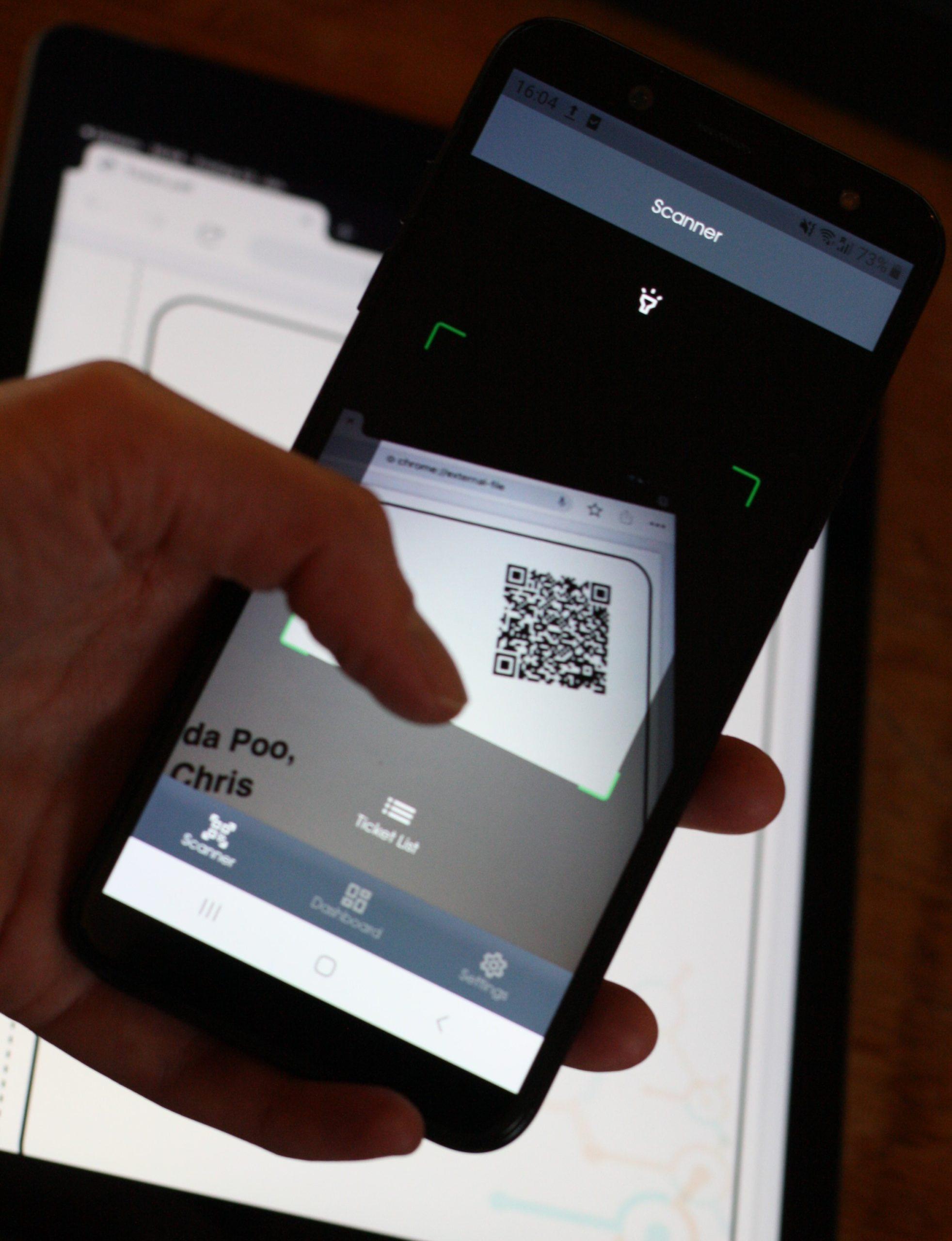 Eine Hand hält ein Smartphone mit der Connfair Admin App und scannt damit den QR-Code eines Online-Tickets auf einem iPad.