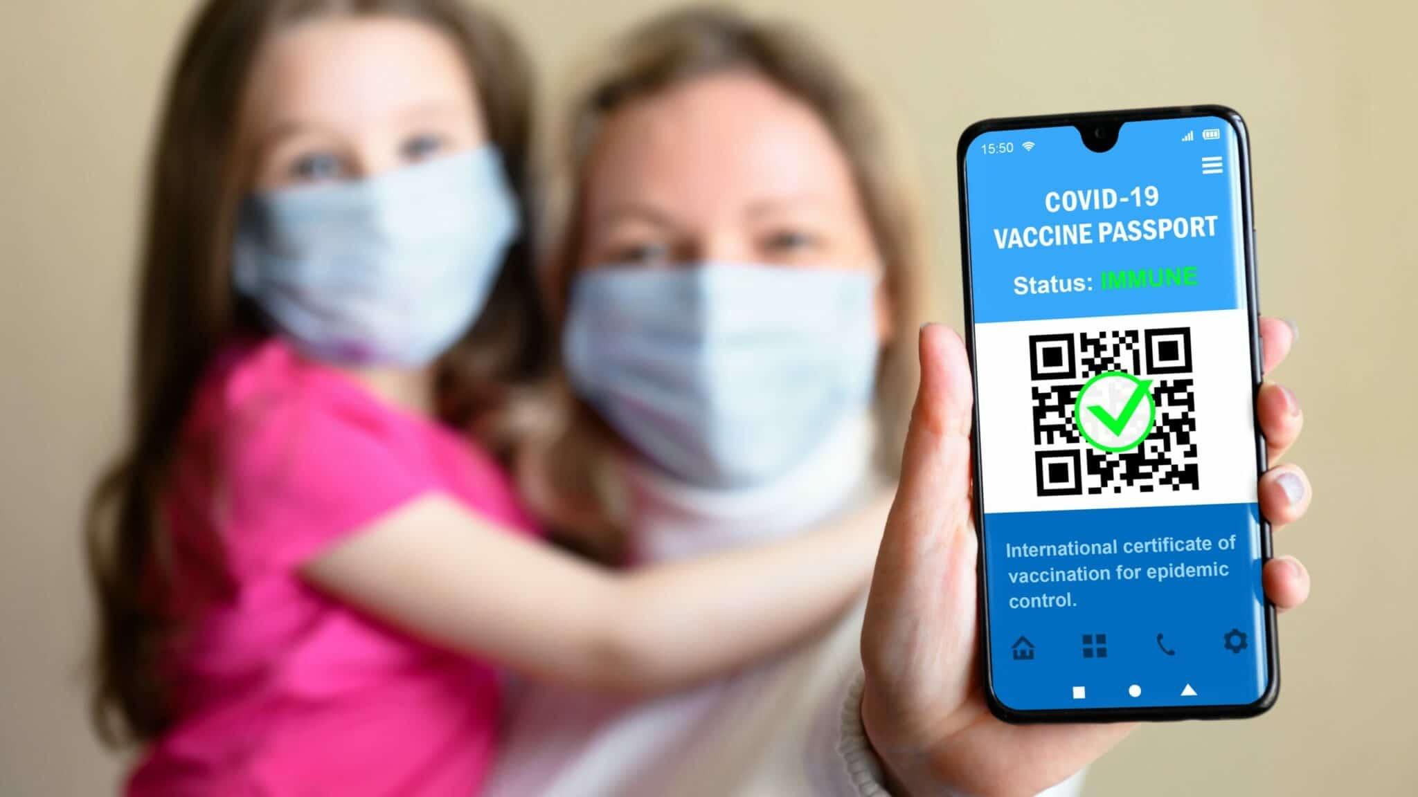 Eine Mutter hält ihre Tochter im Arm und zeigt auf ihrem Smartphone den Covid-Pass vor.