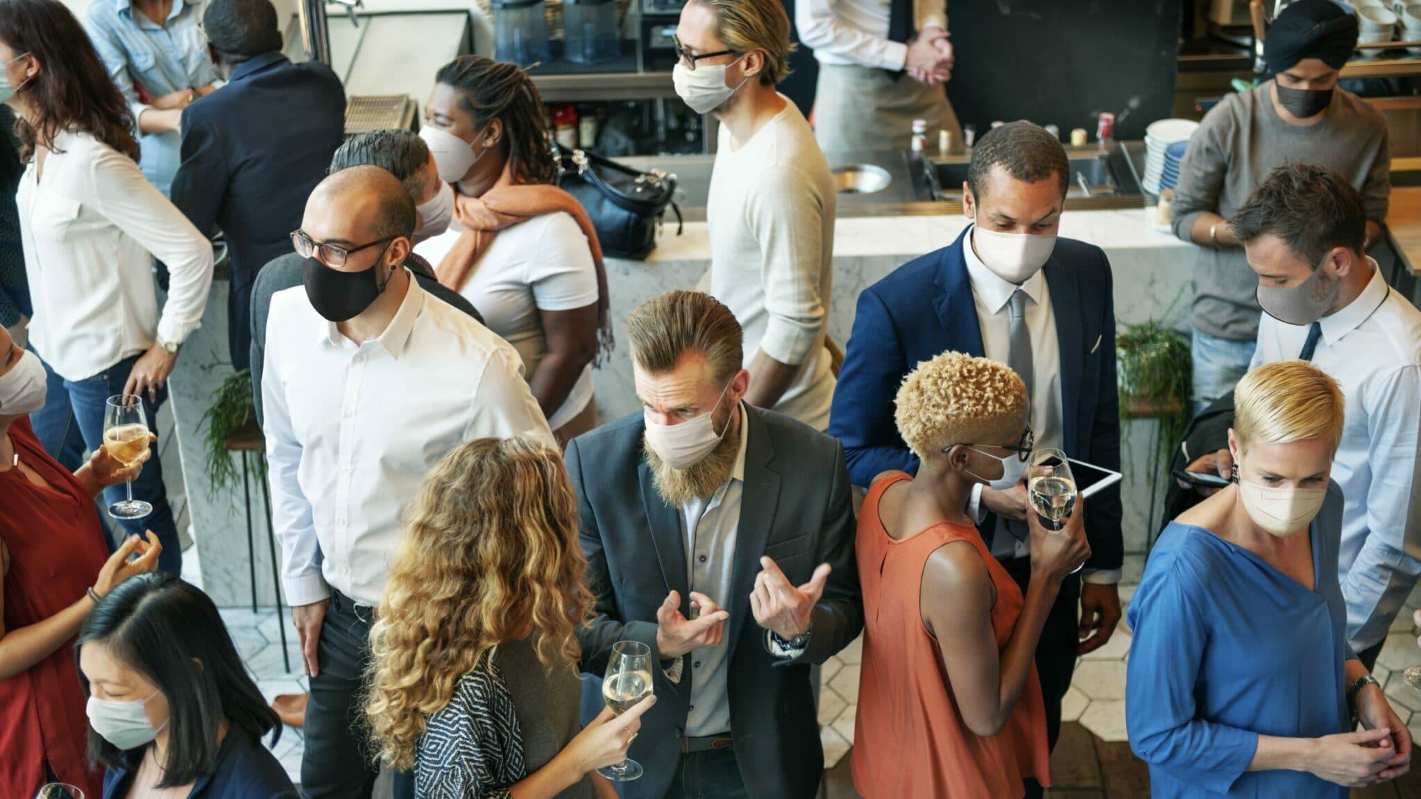 Das Bild zeigt Besucher mit Maske bei einer Veranstaltung unter Corona-Maßnahmen