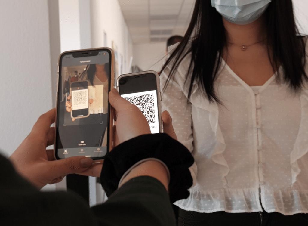 Eine Besucherin betritt eine Veranstaltung und zeigt ein Smartphone mit einem QR-Code auf einem Ticket vor. Der Einlass erfolgt mit einem Smartphone, auf dem die Admin App installiert ist.