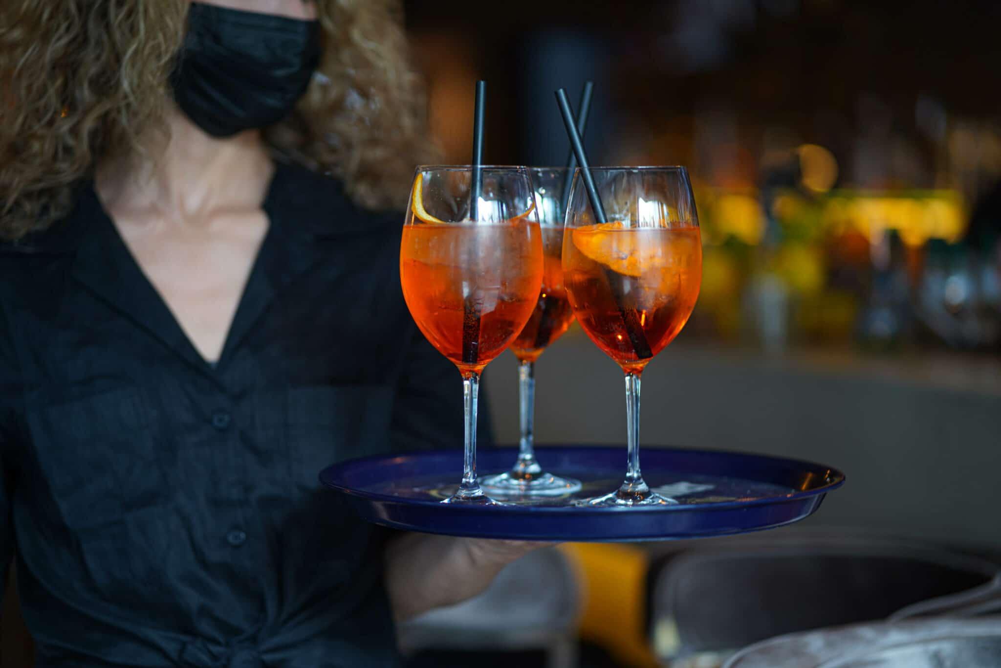 Eine Kellnerin mit Mund-Nasen-Maske trägt ein Tablett mit drei Gläsern Aperol Spritz.