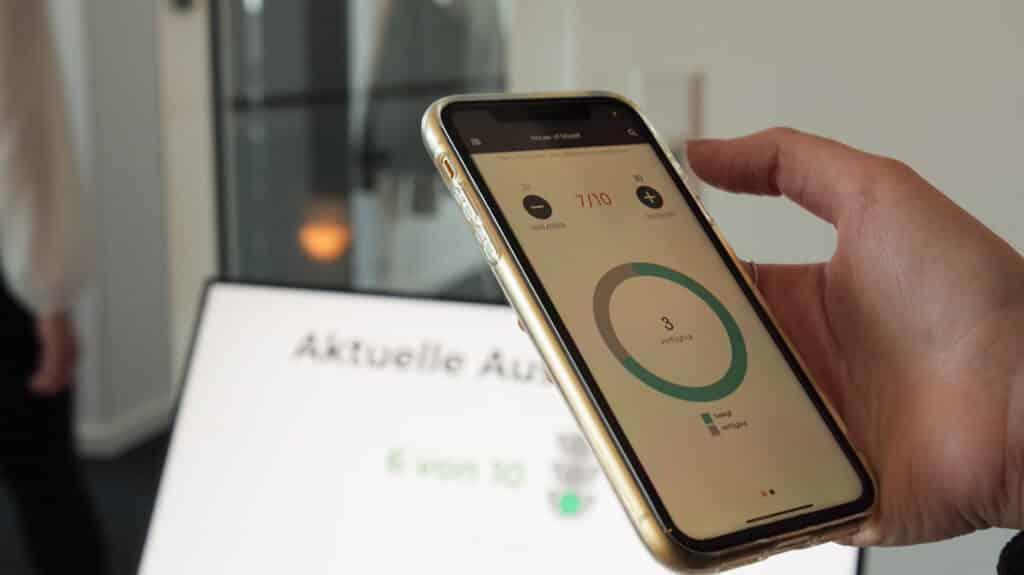 Eine Hand hält ein Smartphone, auf dem ein digitaler Personenzähler für den Einlass bei Veranstaltungen zu sehen ist.